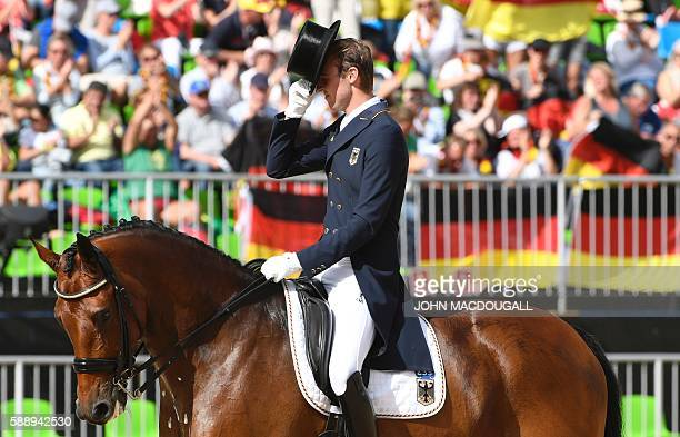 Germany's Sonke Rothenberg on Cosmo salutes the judge after performing his routine during the Equestrian's Dressage Grand Prix team final event of...