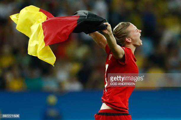 Germany's striker Alexandra Popp runs with a flag as she celebrates her team's victory over Sweden in the Rio 2016 Olympic Games women's football...