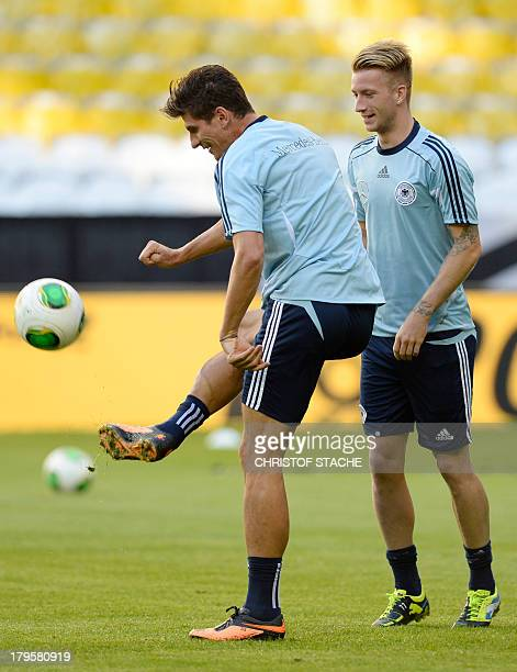Germany's striker Mario Gomez plays the ball beside Germany's midfielder Marco Reus during the final training's session of the German national...