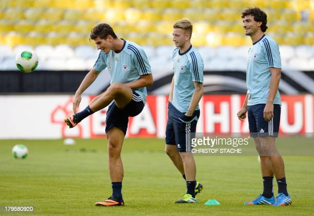 Germany's striker Mario Gomez plays the ball beside Germany's midfielder Marco Reus and Germany's defender Mats Hummels during the final training's...