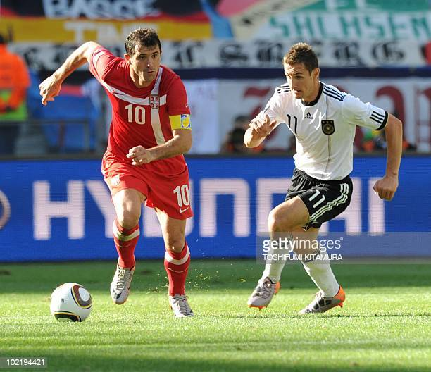 Germany's striker Miroslav Klose fights for the ball with Serbia's midfielder Dejan Stankovic during the Group D first round 2010 World Cup football...