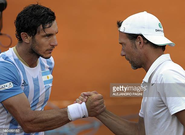 Germany's team captain Carsten Arriens greets Argentina's player Juan Monaco after defeating Florian Mayer the 2013 Davis Cup World Group first round...