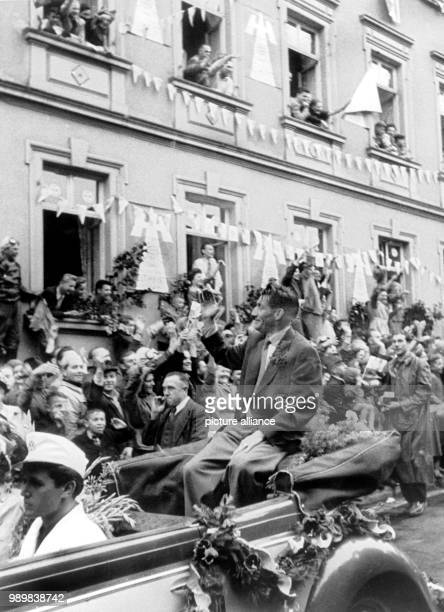 Germany's team captain Fritz Walter is driven through the decorated streets of Kaiserslautern on July 8th 1954 Five of the successful German football...