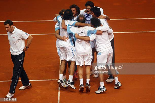 Germany's team captain Patrik Kuehnen walks past celebrating players of Argentina after David Nalbandian and Eduardo Schwank won their doubles match...