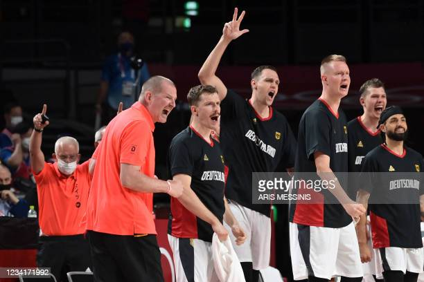 Germany's team coach Henrik Roedl along with players celebrate a point in the men's preliminary round group B basketball match between Germany and...