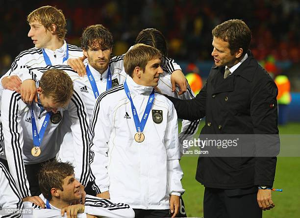 Germany's team manager Oliver Bierhoff congratulates Philipp Lahm as Germany celebrate victory and third place following the 2010 FIFA World Cup...