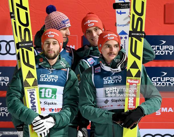 Germany's team Markus Eisenbichler Richard Freitag Stephan Leyhe and Karl Geiger celebrate on the podium after the team event of the FIS Ski Jumping...