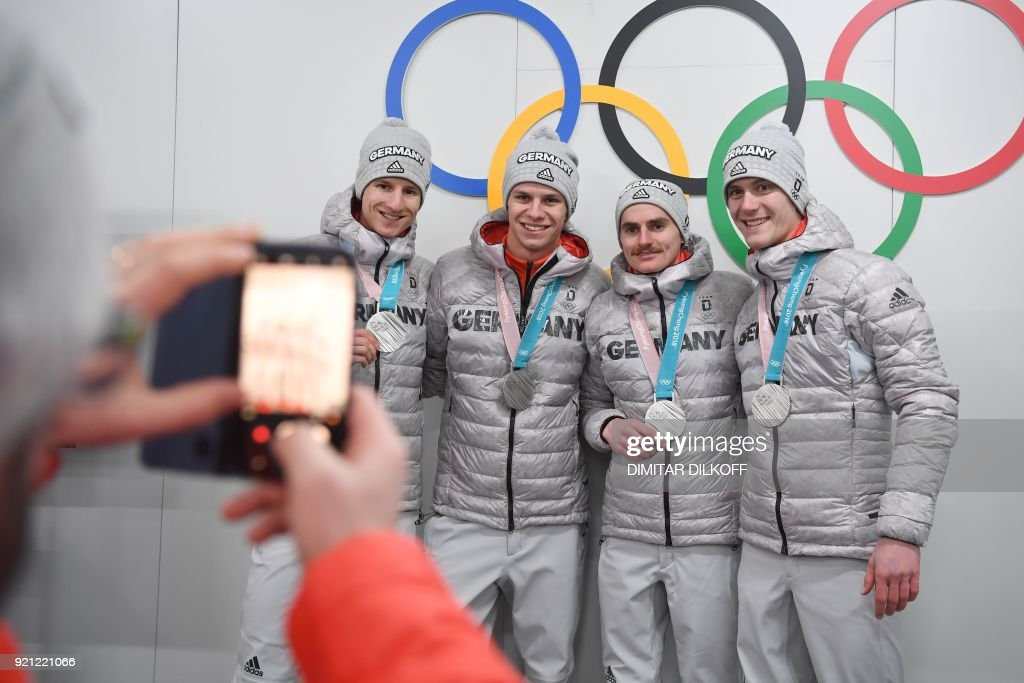 Germany's team ski jumping silver medallists Richard Freitag, Karl Geiger, Stephan Leyhe and Andreas Wellinger pose in front of Olympic rings backstage at the Athletes' Lounge during the medal ceremonies at the Pyeongchang Medals Plaza during the Pyeongchang 2018 Winter Olympic Games in Pyeongchang on February 20, 2018. / AFP PHOTO / Dimitar DILKOFF