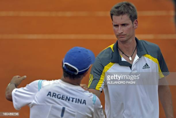 Germany's tennis player Florian Mayer is comforted by Argentina's team captain Martin Jaite after losing against Juan Monaco during the 2013 Davis...