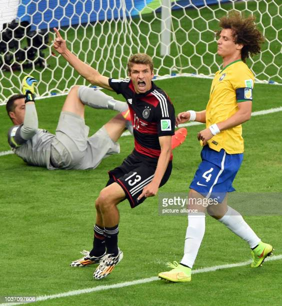 Germany's Thomas Mueller celebrates his 0-1 opening lead goal next to goalkeeper Julio Cesar and David Luiz of Brazil during the FIFA World Cup 2014...