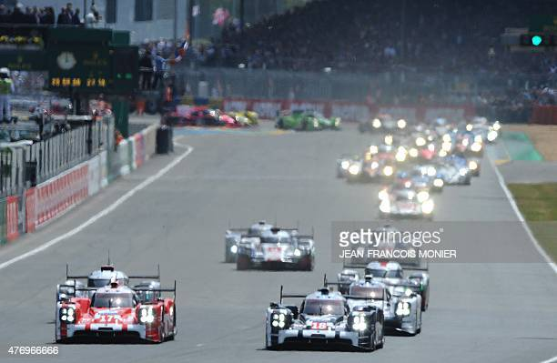 Germany's Timo Bernhard drives his Porsche 919 Hybrid N°17 next to Swiss' Neel Jani on his Porsche 919 Hybrid N°18 ahead Germany's Nico Hulkenberg on...