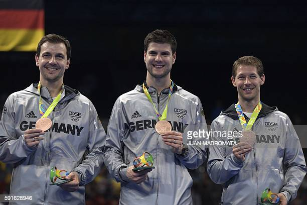 Germany's Timo Boll Germany's Dimitrij Ovtcharov and Germany's Bastian Steger pose with their bronze medals after the final men's team table tennis...