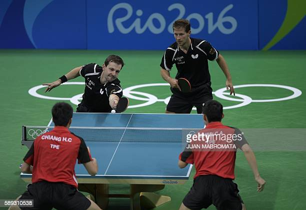 Germany's Timo Boll hits a shot next to Germany's Bastian Steger in the men's team qualification round table tennis match against Taiwan's Chiang...