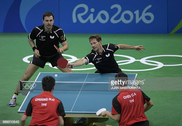 Germany's Timo Boll watches Germany's Bastian Steger hit a shot in the men's team qualification round table tennis match against Taiwan's Chiang...