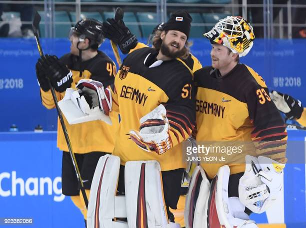 Germany's Timo Pielmeier and Germany's Danny aus den Birken celebrate winning the men's semifinal ice hockey match between Canada and Germany during...