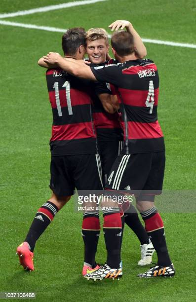 Germany's Toni Kroos celebrates with team mates Miroslav Klose and Benedikt Hoewedes after scoring a goal during the FIFA World Cup 2014 semi-final...