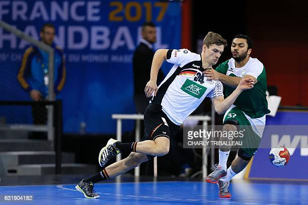 Germany's wing Rune Dahmke works around Saudi Atabia's back Mohammed Alabas during the 25th IHF Men's World Championship 2017 Group C handball match...