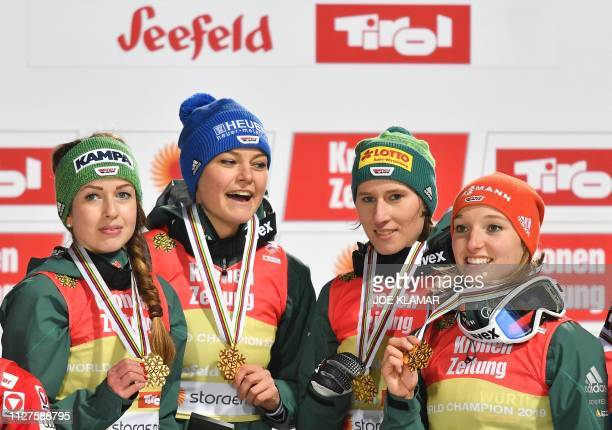 Germany's winning team Juliane Seyfarth Ramona Straub Carina Vogt and Katharina Althaus celebrate with their gold medals on the podium after the...