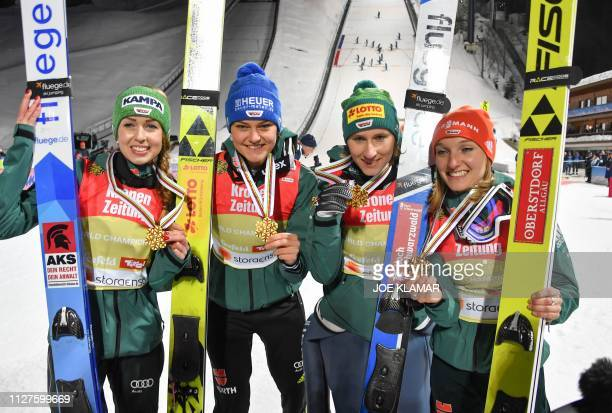 Germany's winning team Juliane Seyfarth Ramona Straub Carina Vogt and Katharina Althaus celebrate with their gold medals after the Ladies team ski...