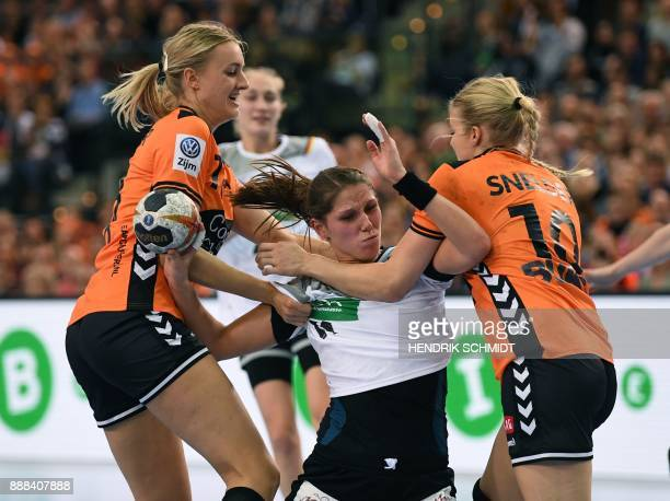 Germany's Xenia Smits vies with Netherland's Kelly Dulfer and Danick Snelder during the preliminary round IHF Womens World Championship handball...