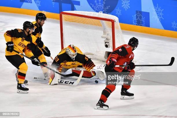 Germany's Yannic Seidenberg , Frank Hoerdler, goalkeeper Danny aus den Birken and Canada's Derek Roy vie for the puck at the men's ice hockey...