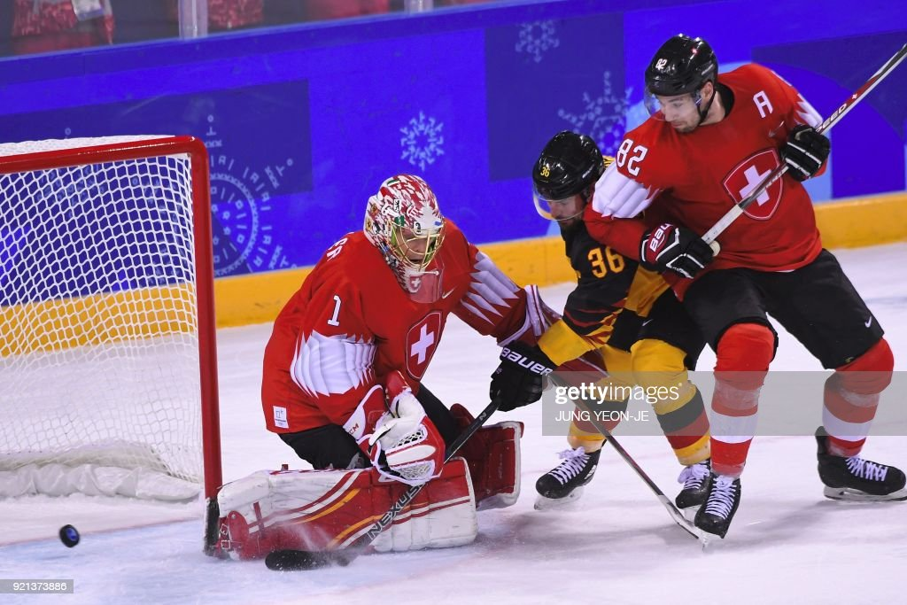 Germany's Yannic Seidenberg (C) scores in overtime in the men's play-offs qualifications ice hockey match between Switzerland and Germany during the Pyeongchang 2018 Winter Olympic Games at the Kwandong Hockey Centre in Gangneung on February 20, 2018. / AFP PHOTO / Jung Yeon-je