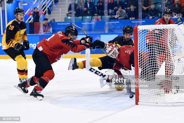TOPSHOT Germany's Yasin Ehliz and Canada's Kevin Poulin look at the puck in the men's semifinal ice hockey match between Canada and Germany during...