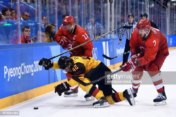 Germany's Yasin Ehliz falls in front of Russia's Ivan Telegin and Pavel Datsyuk in the men's gold medal ice hockey match between the Olympic Athletes...