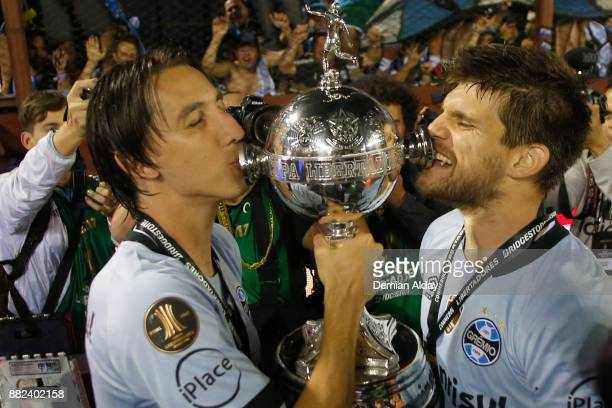 Geromel of Gremio and Walter Kannemann of Gremio celebrate with the trophy after winning the second leg match between Lanus and Gremio as part of...