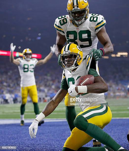 Geronimo Allison of the Green Bay Packers celebrates his touchdown catch with teammate Jared Cook against the Detroit Lions during fourth quarter at...