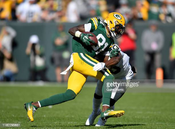 Geronimo Allison of the Green Bay Packers is tackled in the second quarter by Daryl Worley of the Oakland Raiders at Lambeau Field on October 20 2019...