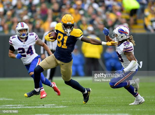 Geronimo Allison of the Green Bay Packers runs between Taron Johnson of the Buffalo Bills and Ryan Lewis during the third quarter of a game at...