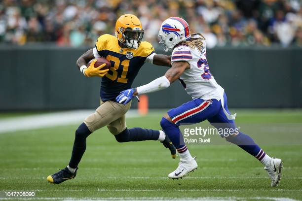 Geronimo Allison of the Green Bay Packers runs with the ball while being chased by Ryan Lewis of the Buffalo Bills in the second quarter at Lambeau...