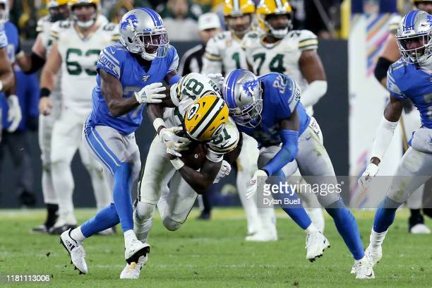 Geronimo Allison of the Green Bay Packers runs with the ball while being tackled by Justin Coleman and Tavon Wilson of the Detroit Lions in the...