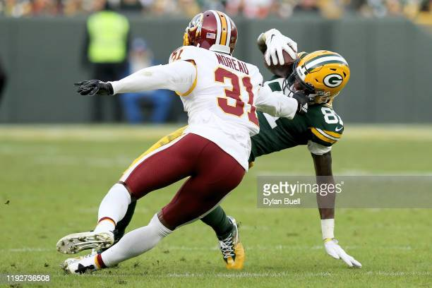 Geronimo Allison of the Green Bay Packers slides while being tackled by Fabian Moreau of the Washington Redskins in the fourth quarter at Lambeau...