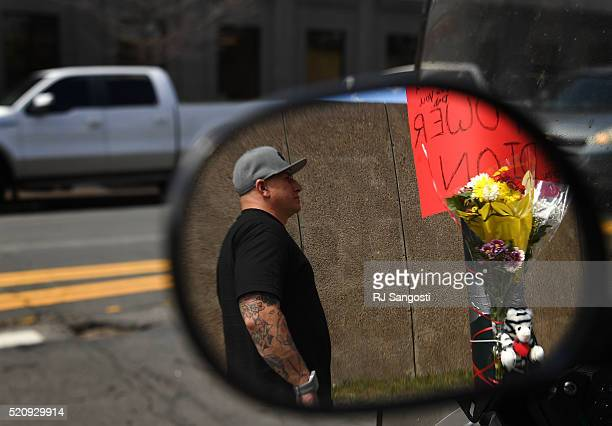 Geronimo Barrientos is reflected in the mirror of a motorcycle parked nearby as he visits the spot where his brother was shot in downtown April 13...