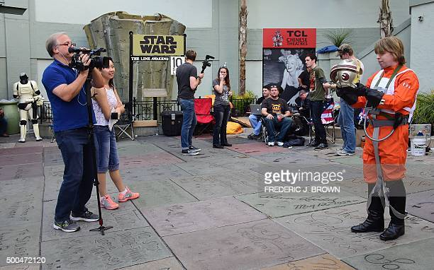 Gerrard Christian Zacher, dressed in a Luke Skywalker X-Wing Pilot outfit, displays the helmet for a camera crew on hand to interview fans, among a...