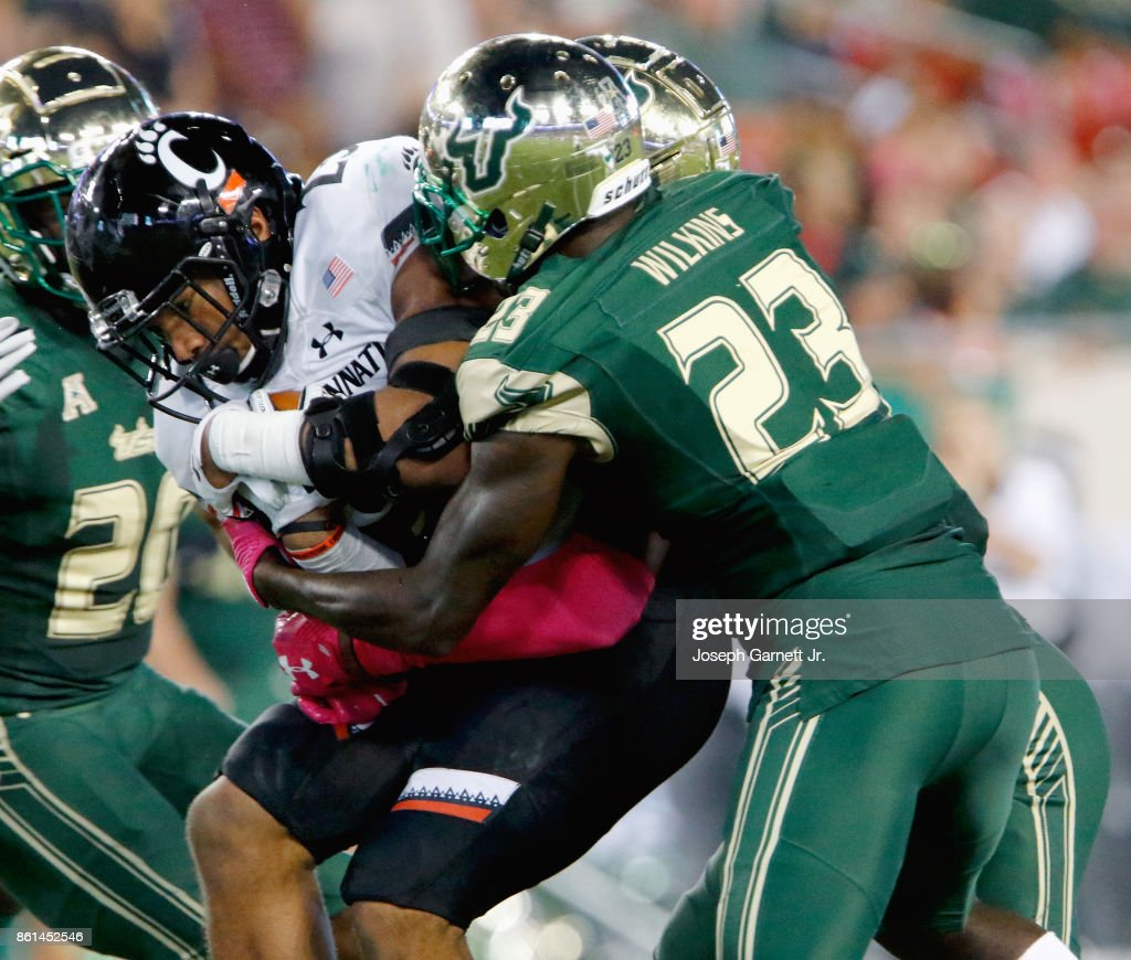 Gerrid Doaks #23 of the Cincinnati Bearcats collides with Mazzi Wilkins #23 of the South Florida Bulls wihile running the ball during the second quarter of their game at Raymond James Stadium on October 14, 2017 in Tampa, Florida.