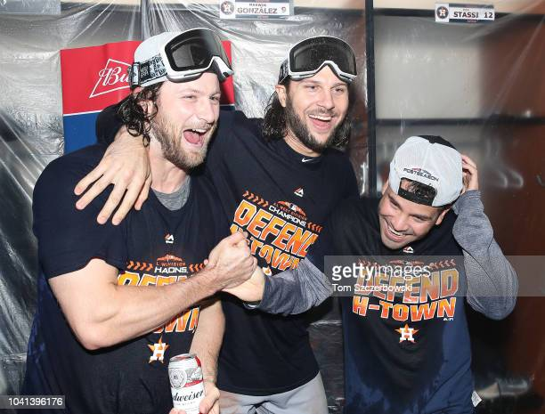 Gerrit Cole of the Houston Astros celebrates in the clubhouse with Jake Marisnick and Jose Altuve after the Astros clinched the American League West...