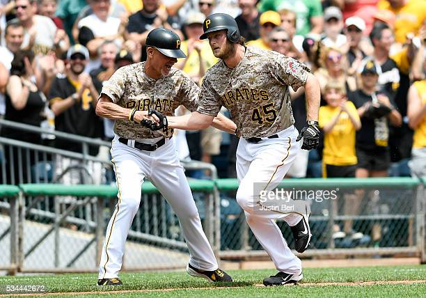 Gerrit Cole of the Pittsburgh Pirates is greeted by third base coach third base coach Rick Sofield after hitting a three run home run in the second...