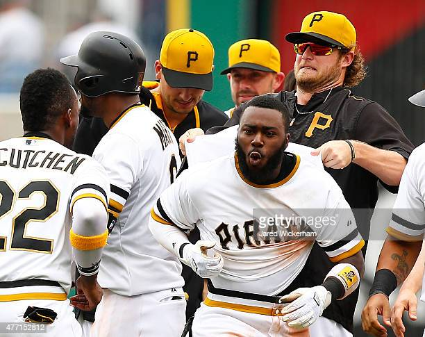 Gerrit Cole of the Pittsburgh Pirates pulls on the jersey of his teammate Josh Harrison after Harrison hit the gamewinning RBI single in the 11th...