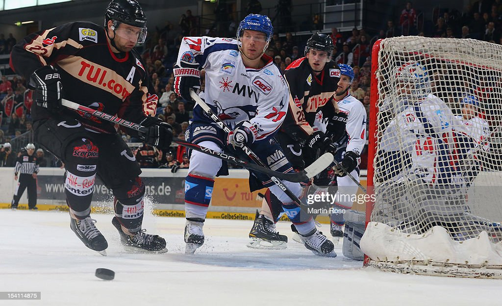 Gerrit Fauser (L) of Hannover and Adam Mitchell(C) of Mannheim battle for the puck during the DEL match between Hannover Scorpions and Aadler Mannheim at TUI Arena on October 14, 2012 in Hanover, Germany.
