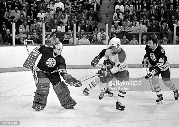 Gerry Cheevers of the Boston Bruins makes a glove save during a game against the Montreal Canadiens at the Montreal Forum circa 1970 in Montreal,...