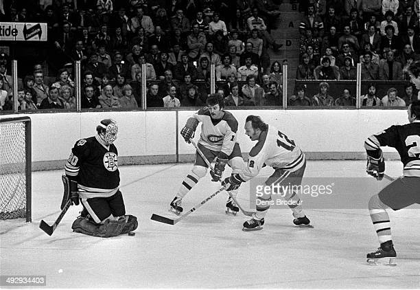 Gerry Cheevers of the Boston Bruins makes the save on a shot by Yvan Cournoyer of the Montreal Canadiens during a game at the Montreal Forum circa...