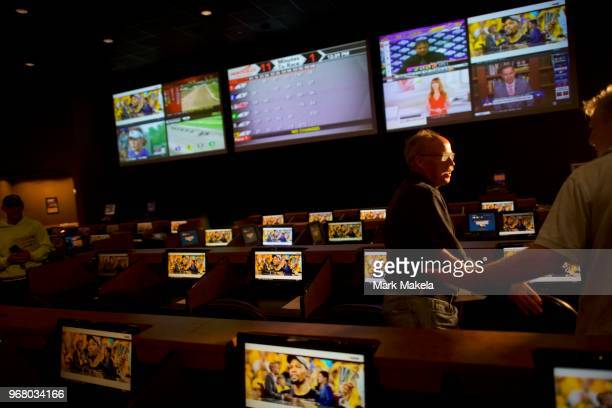 Gerry Dennison speaks with a friend placing his bet at Dover Downs Casino on June 5, 2018 in Dover, Delaware. Delaware is the first state to launch...