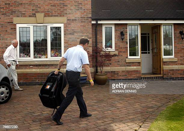 Gerry McCann carries a childrens' car seat into his house after arriving home from Portugal to Rothley Leicestershire 09 September 2007 The parents...