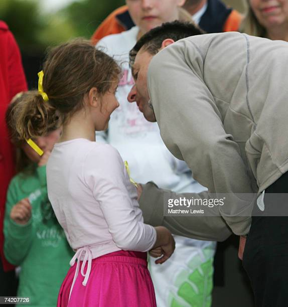 Gerry McCann gives a young girl a kiss after she gave him a prayer in support for his daughter Madeleine McCann at the War memorial in Rothley...
