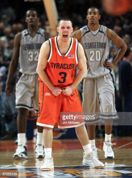 Gerry McNamara of the Syracuse Orange celebrates after the final basket by Syracuse to win the game as Jeff Green and Darrel Owens of the Georgetown...