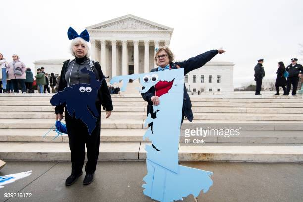 Gerrymandering activists Helenmary Ball, left, posing as MD district 5, and Rachael Lemberg, posing as MD district 1, gather on the steps of the...