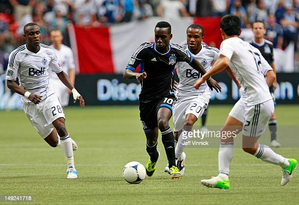 Gershon Koffie Dane Richards and YoungPyo Lee of the Vancouver Whitecaps FC look on as Simon Dawkins of the San Jose Earthquakes dribbles the ball...